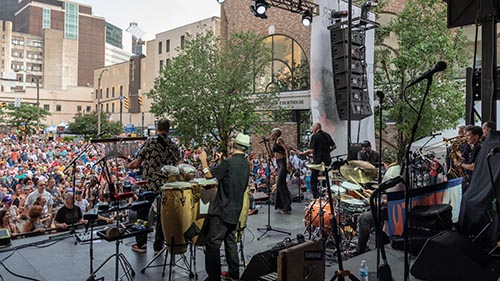 Community Soul Project band performs onstage in Rochester before a large outdoor audience