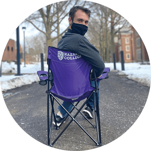 student sitting in a Nazareth camp chair
