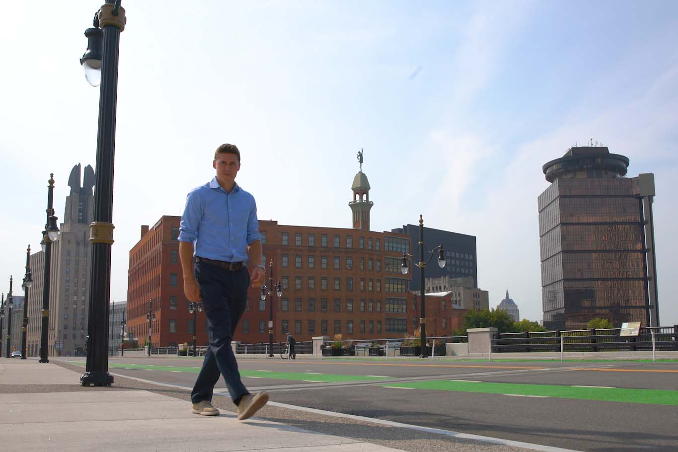 Daniel Jacob walks on sidewalk with downtown Rochester cityscape behind him