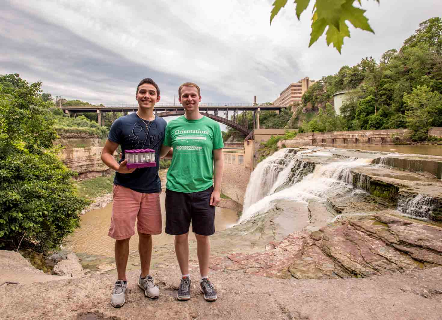 Two student researchers with test tubes at Rochester's Lower Falls