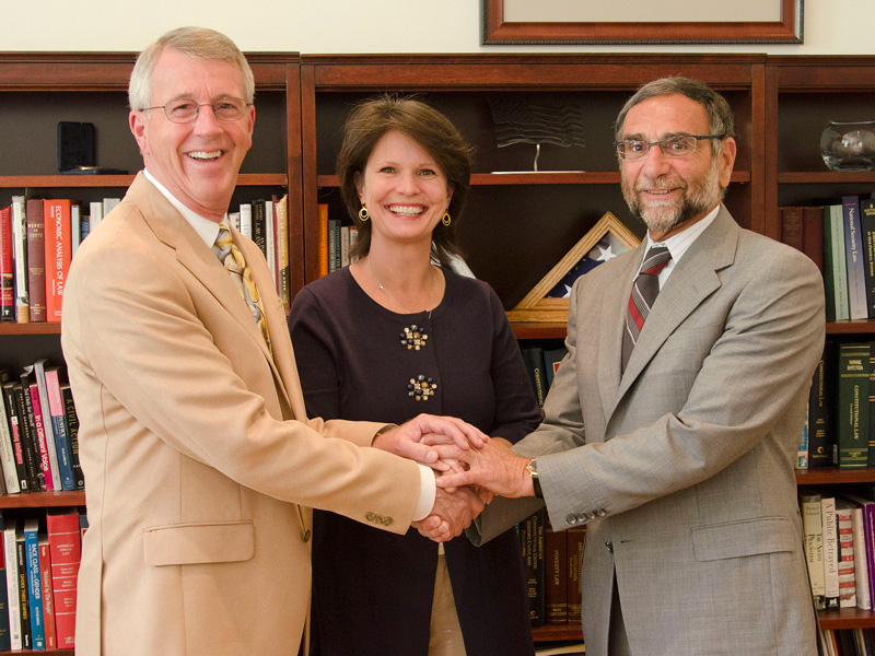 Larry and Nancy Peckham shaking hands with Nazareth College President Daan Braveman.