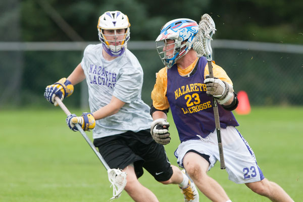 Two lacrosse players running on the field.