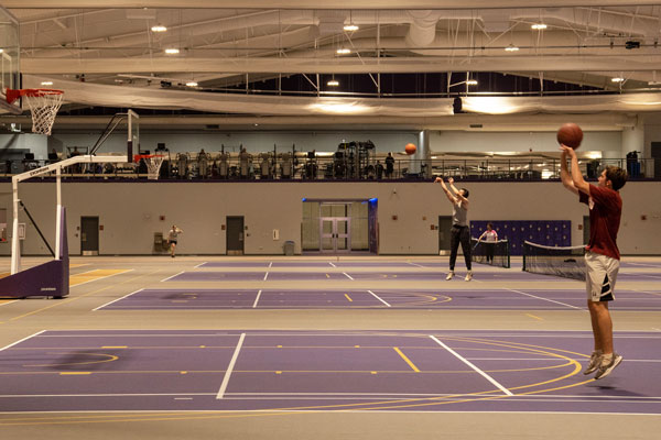 Students shooting hoops on basketball courts inside an indoor track