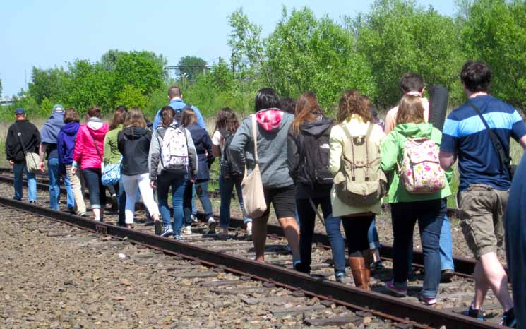 The March participants walk along railroad tracks.
