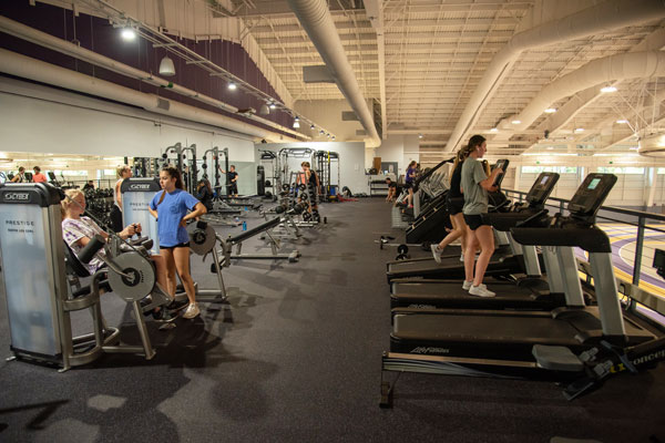 students using weight machines and treadmills, overlooking an indoor track